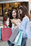 счастливая азиатская женщина с smartphone и красочными хозяйственными сумками на Стоковая Фотография