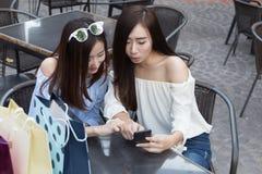 счастливая азиатская женщина с smartphone и красочными хозяйственными сумками на Стоковые Изображения RF
