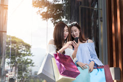счастливая азиатская женщина с smartphone и красочными хозяйственными сумками на Стоковое Изображение