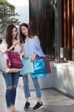 счастливая азиатская женщина с smartphone и красочными хозяйственными сумками на Стоковое фото RF