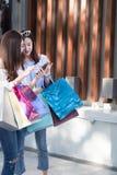 счастливая азиатская женщина с smartphone и красочными хозяйственными сумками на Стоковые Изображения