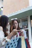 счастливая азиатская женщина с smartphone и красочными хозяйственными сумками на Стоковые Фотографии RF