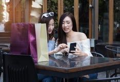 счастливая азиатская женщина с smartphone и красочными хозяйственными сумками на Стоковые Фото