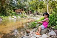 Счастливая азиатская китайская маленькая девочка двигая под углом с рыболовной удочкой Стоковые Фото