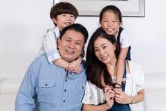 Счастливая азиатская китайская семья сидя на усмехаться кресла Стоковые Фото