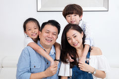 Счастливая азиатская китайская семья сидя на усмехаться кресла Стоковое Изображение RF