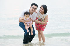 Счастливая азиатская семья играя на внешнем пляже песка стоковое фото rf