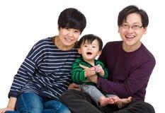 Счастливая азиатская семья усмехаясь совместно стоковые изображения rf