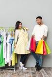 Счастливая дама выбирая одежды приближает к человеку держа хозяйственные сумки Стоковая Фотография
