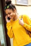 Счастливая африканская женщина идя и говоря на мобильном телефоне Стоковое Фото