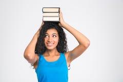 Счастливая афро американская женщина держа книги на голове Стоковые Фотографии RF