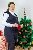 Счастливая беременная женщина держа форму сердца стоковые фото