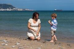 Счастливая беременная женщина играя с мальчиком ребенка на пляже Стоковая Фотография RF