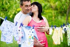 Счастливая беременная женщина и ее супруг в парке Стоковая Фотография