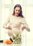 Счастливая беременная женщина подготавливая еду дома Стоковое Изображение RF