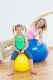 Счастливая беременная женщина работая на шарике тренировки с молодой дочерью Стоковая Фотография