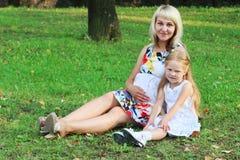 Счастливая беременная женщина с дочерью сидит на зеленой траве Стоковая Фотография