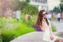 Счастливая беседа девушки smartphone outdoors в парке Молодая привлекательная женщина с мобильным телефоном outdoors наслаждаясь  Стоковые Фото