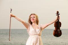 Счастливая белокурая девушка с скрипкой напольной Стоковая Фотография