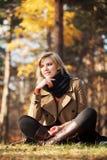 Счастливая белокурая женщина в лесе осени стоковая фотография