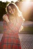 Счастливая белокурая модель в модном checkered платье представляя на стоковые фотографии rf