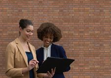 Счастливая бизнес-леди используя таблетку против кирпичной стены Стоковое Изображение RF