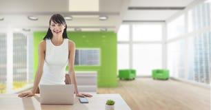 Счастливая бизнес-леди на столе используя компьютер стоковое фото rf