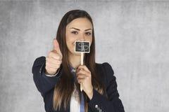 Счастливая бизнес-леди покрывает ее рот с знаком доллара, большим пальцем руки Стоковая Фотография RF