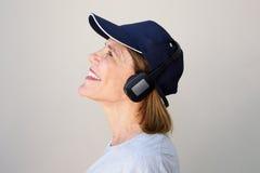 Счастливая более старая женщина наслаждаясь музыкой с наушниками Стоковые Фото