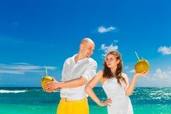 Счастливая вода кокоса питья жениха и невеста на тропическом пляже W Стоковое Фото