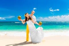 Счастливая вода кокоса питья жениха и невеста на тропическом пляже W Стоковые Изображения