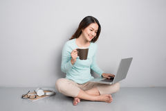 Счастливая вскользь красивая азиатская женщина работая на компьтер-книжке сидя o Стоковое Изображение
