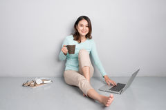 Счастливая вскользь красивая азиатская женщина работая на компьтер-книжке сидя o Стоковая Фотография RF