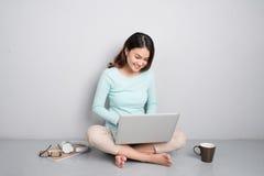 Счастливая вскользь красивая азиатская женщина работая на компьтер-книжке сидя o Стоковые Фотографии RF