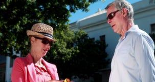 Счастливая встреча и женщина пар показывая ее приобретения к партнеру сток-видео