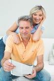 Счастливая газета чтения пар в живущей комнате Стоковые Фото