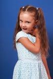 Счастливая гримасничая девушка ребенк представляя в голубом платье моды Крупный план p стоковые изображения rf