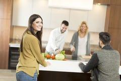 Счастливая группа в составе молодые человеки и женщины в современной кухне стоковое изображение rf