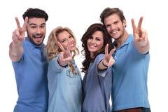 Счастливая группа в составе молодые люди делая победу Хан Стоковые Фотографии RF