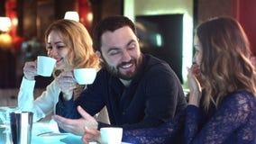 Счастливая группа в составе друзья или коллеги дела беседуя и смеясь над совместно в баре сток-видео