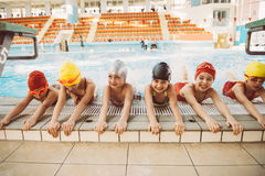 Счастливая группа детей детей на классе бассейна уча поплавать Стоковая Фотография