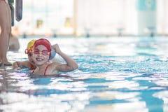 Счастливая группа детей детей на классе бассейна уча поплавать Стоковые Изображения