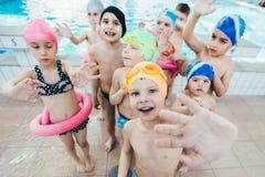 Счастливая группа детей детей на классе бассейна уча поплавать Стоковая Фотография RF