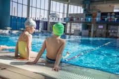 Счастливая группа детей детей на классе бассейна уча поплавать Стоковые Фото