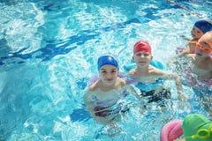 Счастливая группа детей детей на классе бассейна уча поплавать Стоковые Фотографии RF