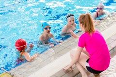 Счастливая группа детей детей на классе бассейна уча поплавать Стоковое Изображение