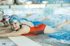 Счастливая группа детей детей на классе бассейна уча поплавать Стоковые Изображения RF