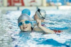Счастливая группа детей детей на классе бассейна уча поплавать Стоковое фото RF