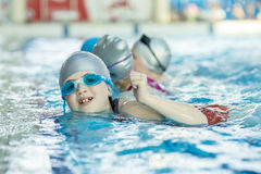 Счастливая группа детей детей на классе бассейна уча поплавать Стоковое Изображение RF