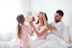 Счастливая девушка давая цветки к матери в кровати дома стоковое изображение